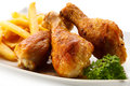 Roasted chicken drumsticks with chips legs and vegetables Stock Image