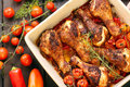 Roasted chicken drumsticks with vegetables in a pan on wooden background Stock Photos
