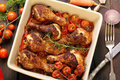 Roasted chicken drumsticks with vegetables in a pan on wooden background Stock Images