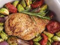 Roasted chicken fillet with vegetables, brussels sprouts, onions, tomato close up Royalty Free Stock Photo