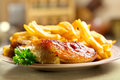 Roasted chicken leg with fries potato on a plate Royalty Free Stock Photos
