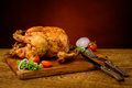 Roasted chicken meat still life with and vegetables on a wooden plate Royalty Free Stock Photography