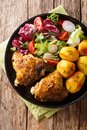 Roasted chicken thighs with new potatoes and fresh salad close-up on the plate. Vertical top view Royalty Free Stock Photo