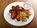 Roasted chicken wings on plate shallow depth of field Stock Photos