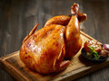 Roasted chicken on wooden cutting board Royalty Free Stock Photo