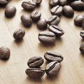 Roasted coffee beans closeup of a pile of on a wooden table Stock Photos