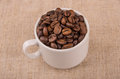 Roasted coffee beans in coffeecup on burlap Royalty Free Stock Photo
