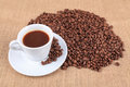 Roasted coffee beans and cup a of on linen cloth background Royalty Free Stock Images