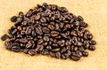Roasted coffee beans on sack cloth background Royalty Free Stock Images
