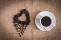 Roasted coffee beans in the shape of a heart and coffee cup Royalty Free Stock Photo