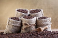 Roasted coffee beans in small burlap bags on golden background Stock Photography