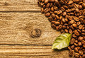 Roasted coffee beans on textured rustic wood pile of fresh arranged as a corner border boards with a green leaf and Stock Photos