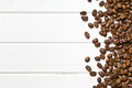 Roasted coffee beans top view of on white wooden background Royalty Free Stock Photo