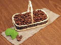 Roasted coffee beans in wicker basket Stock Images