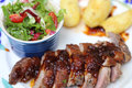 Roasted duck breast with green salad and roast potatoes Royalty Free Stock Photo