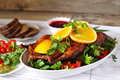 Roasted duck with orange berry sauce vegetables and bread on a wood table Stock Images