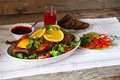 Roasted duck with orange berry sauce vegetables and bread on a wood table Stock Photo