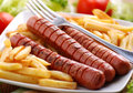 Roasted frankfurters with french fries on dish Royalty Free Stock Photo