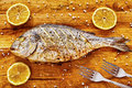 Roasted gilt head bream fish on a wooden table. Royalty Free Stock Photo