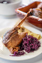 Roasted goose leg with red cabbage and potatoe pancakes on white plate, traditional food Royalty Free Stock Photo