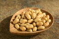 Roasted peanuts peeled unsalted on small bamboo plate photographed on slate with natural light selective focus focus one third Stock Images