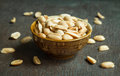 Roasted peeled salted peanuts in rustic bowl on wooden background Royalty Free Stock Photo
