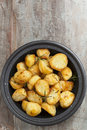 Roasted potatoes with rosemary in black dish and sea salt flakes timber background Stock Image