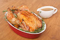 Roasted rosemary turkey in a dish with gravy whole stuffing on wooden table Stock Image