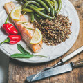Roasted salmon with quinoa, chilli pepper and poached beans Royalty Free Stock Photo