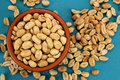 Roasted salted peanuts in bowl  on blue background, top view Royalty Free Stock Photo