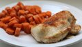 Roasted and seasoned chicken breast with carrots plate of on the side Royalty Free Stock Photo