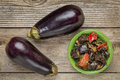 Roasted spicy eggplant salad with bell pepper and two fresh fruits top view on a rustic wood table Royalty Free Stock Images