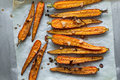 Roasted spring carrots on parchment with garlic, pepper peas and coriander