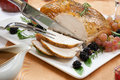 Roasted turkey breast rosemary basil rub carving garnished with grapes blackberies and fresh and in fall themed Royalty Free Stock Image