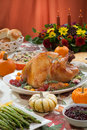 Roasted turkey on harvest table a server tray garnished with fresh figs grape kumquat and herbs fall red wine side dishes pie Royalty Free Stock Images