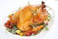 Roasted turkey on tray over white garnished with red grapes figs kumquat and herbs background Royalty Free Stock Photos