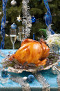 Roasted turkey for white christmas garnished with herbs on blue decorations and champagne tree as background Royalty Free Stock Photos