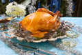 Roasted turkey for white christmas garnished with herbs on blue decorations and champagne tree as background Stock Photo