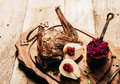 Roasted venison haunch with pears on wooden tray angled view of prepared rustic table evergreen sprigs and deer antlers Stock Photo