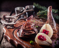 Roasted vension haunch served on wooden tray with prepared pears accented by evergreen sprigs and deer antlers Royalty Free Stock Image