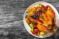 Roasted whole chicken, potatoes, baby carrots, eggplants, green Royalty Free Stock Photo