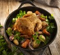Roasted whole chicken with vegetables in a cast iron pan Royalty Free Stock Photo