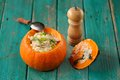 Roasted whole pumpkin with rice and meat with pepper mill Royalty Free Stock Photo