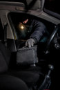 Robber breaking a car s windows to steal bag with mask on his face holds the battery and looks what will the night time Royalty Free Stock Image