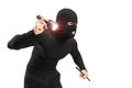 Robber holding a flashlight and piece of pipe Stock Photo