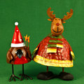 Robin and reindeer christmas decorations pair of metal rudolph the red nosed reindder on green Stock Images