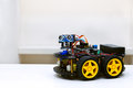 Robot with four wheels stands on a white table Royalty Free Stock Photo