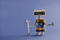 Robot serviceman with hand wrench and screwdriver on blue background. Abstract mechanical toy worker made of electronic