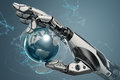 Robotic arm holding earth globe with mechanical fingers.