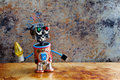 Robotic toy character with yellow lamp in hand, standing rusty iron surface. Vintage textured wall backdrop. Shallow
